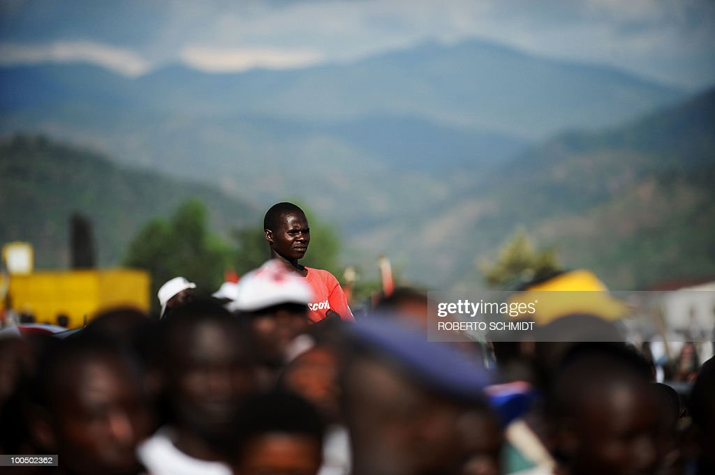 A Burundian man raises himself above a crowd of thousands to get a better view at a political rally for the ruling party at a local soccer field in Bujumbura on May 11, 2010. Some 3.5 million registered voters will go to the polls to elect 1,935 municipal counselors across the country on May 20th in what experts agree will be a catlyst for the soon to follow Legislative and Presidential elections. This elections will be the fist all inclusive elections since a peace accord ended a bloody 13 year civil war in 2006. The French government has provided Burundi with 90,000 euros to organize the upcomming elections.