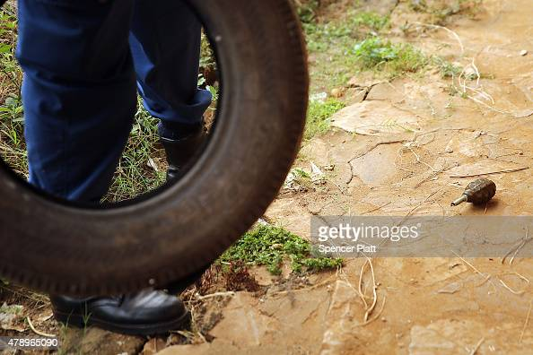 Burundian police officer stands near an unexploded grenade at a polling station during parliamentary and local elections on June 29 2015 in Bujumbura...
