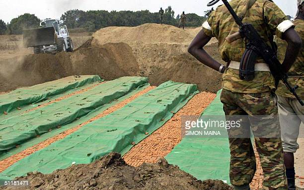 Burundian soldier stands next to a mass grave as UN personel covers the grave in Gatumba 17 August 2004 Tiny Rwanda and Burundi have threatened...