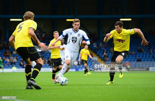 Bury's Danny Mayor in action with Burton Albion's George Taft and John Mousinho