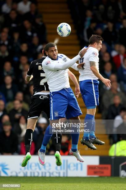 Bury's Leon Clarke beats Wigan Athletic's Chris McCann in the air