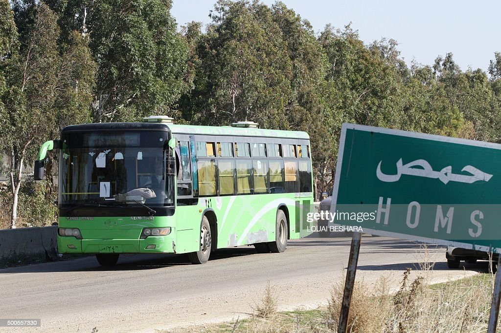 A bus carrying Syrian rebel fighters leaves the city of Homs on December 9 as hundreds of civilians and rebel forces began evacuating the last...