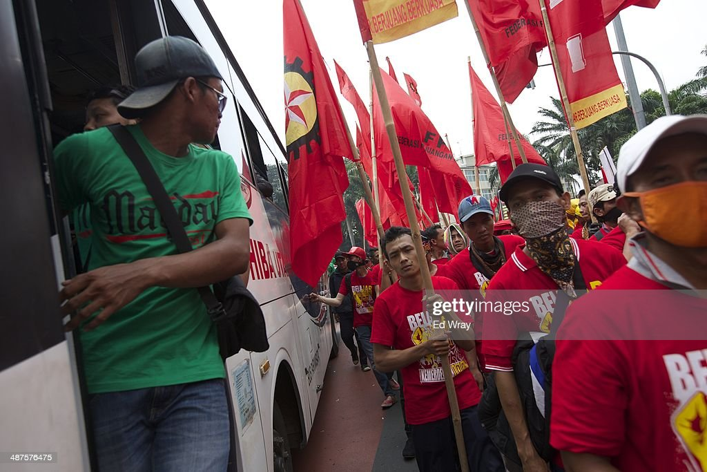 A bus conductor watches from his bus as members of Indonesian Labour unions and labour activists march on a street in the central business district on May 1, 2014 in Jakarta, Indonesia. Protesters across Indonesia have organised rallies to demand higher wages, as Indonesia recognises its first national labour day holiday.
