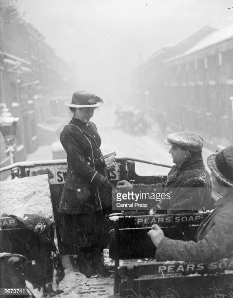 A bus conductress at work on the top deck of an opentop bus in the snow during World War I
