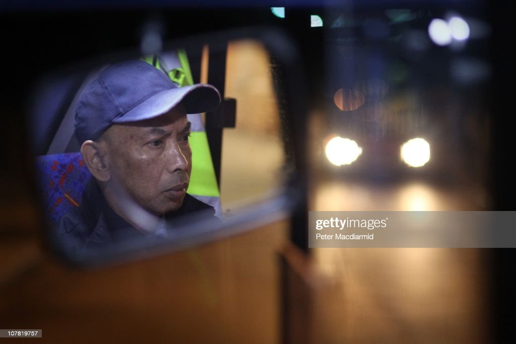 Bus driver Chitpinit Kaewchaluay is reflected in his rear view mirror as he drives the 762 night bus on December 15 2010 in London England Chitpinit...