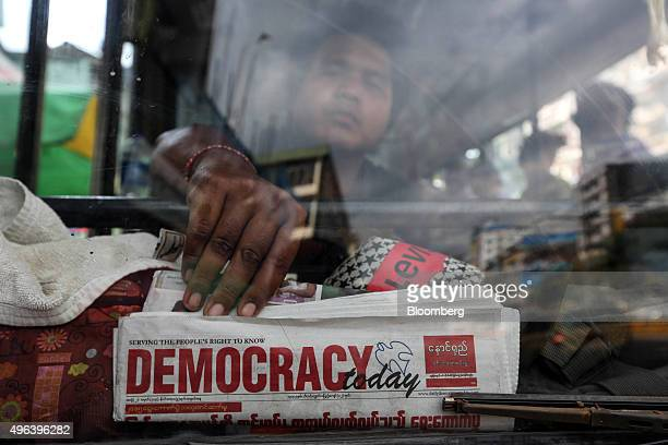 A bus driver holds a Democracy Today newspaper behind the window of his bus at a bus station in Yangon Myanmar on Monday Nov 9 2015 The spirit of NLD...
