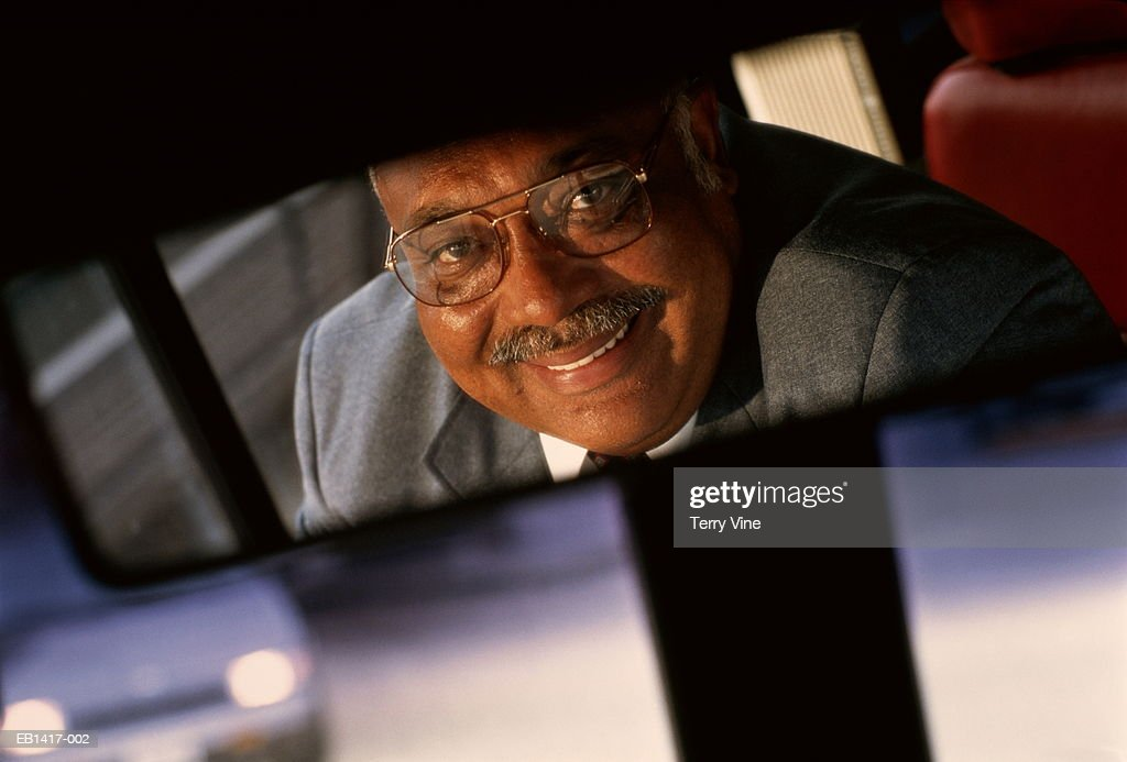 Bus driver in rear-view mirror, portrait