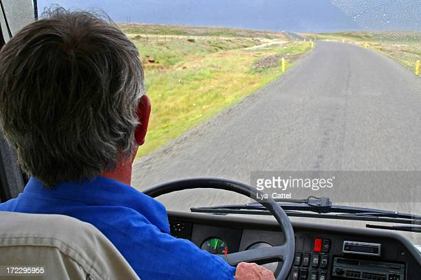 Bus driver on empty road with rainy weather
