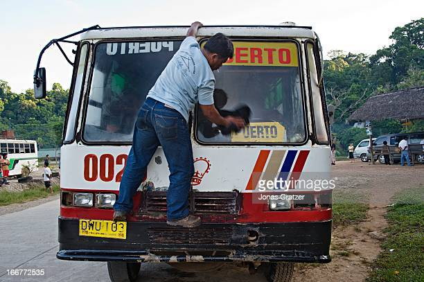 EL NIDO PALAWAN PHILIPPINES A bus driver washes the windshield of his bus before departure