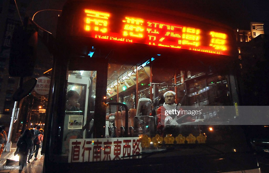 A bus driver works dressed in a Christmas themed outfit in Taipei on December 24, 2012. The driver was taking part in a campaign to celebrate the upcoming Christmas. AFP PHOTO / Mandy CHENG