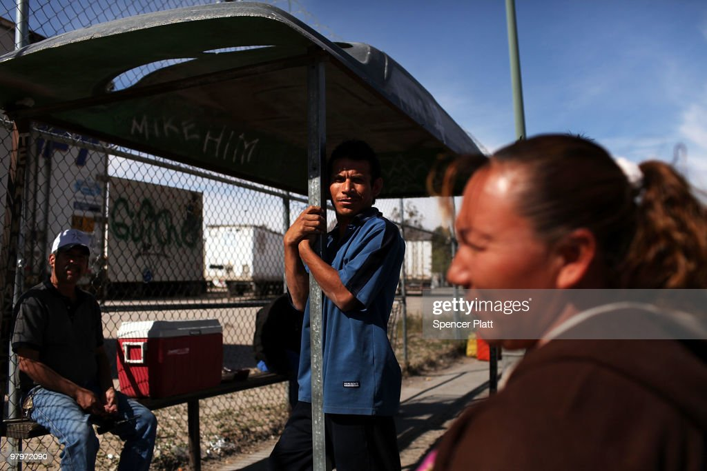 Bus drivers and food vendors wait for business in front of a maquiladora, or factory, on March 23, 2010 in Juarez, Mexico. Secretary of State Hillary Rodham Clinton, Defense Secretary Robert Gates, and Homeland Security Secretary Janet Napolitano will all visit Mexico on Tuesday for discussions centered on Mexico�s endemic drug-related violence. The border city of Juarez has suffered from the duel effects of the recession in America and the surge in drug violence. An estimated 100,000 jobs having been lost since the recession and some 10,000 businesses have been closed in the past 18 months. City officials also say that thousands of homes have been abandoned as residents leave for El Paso or safer cities in Mexico. Juarez has been racked by violent drug related crime recently and has quickly become one of the most dangerous cities in the world to live. As drug cartels have been fighting over ever lucrative drug corridors along the United States border, the murder rate in Juarez has risen to 173 slayings for every 100,000 residents. President Felipe Calderon�s strategy of sending 7000 troops to Juarez has not mitigated the situation. With a population of 1.3 million, 2,600 people died in drug-related violence last year and 500 so far this year, including two Americans recently who worked for the U.S. Consulate and were killed as they returned from a children�s party.