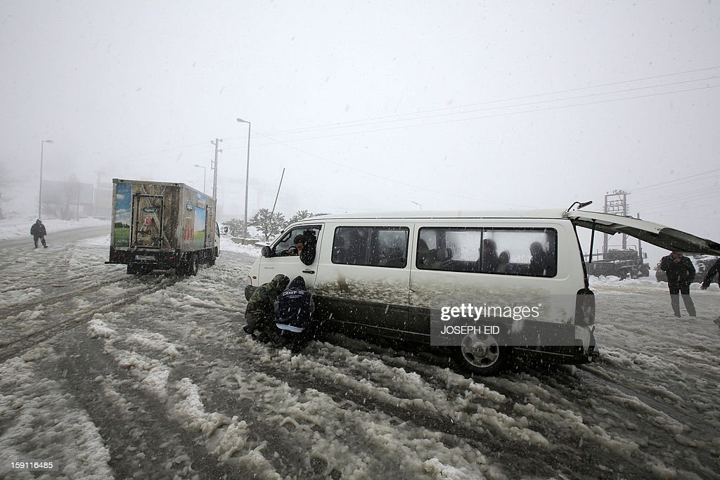 Bus drivers place metal chains on the tires of their vehicles at the area of Dahr al-Baidar before driving on the main highway linking Beirut to Damascus, on January 8, 2013. Stormy weather, including high winds and heavy rainfall, lashed the eastern Mediterranean coast, downing power lines and trees and causing several injuries in a number of countries. AFP PHOTO /JOSEPH EID