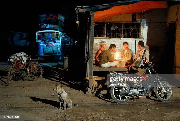 Bus drivers talk about work at night over candlelight in a darkened street in Mandalay Much of the city goes pitch black at night a result of the...