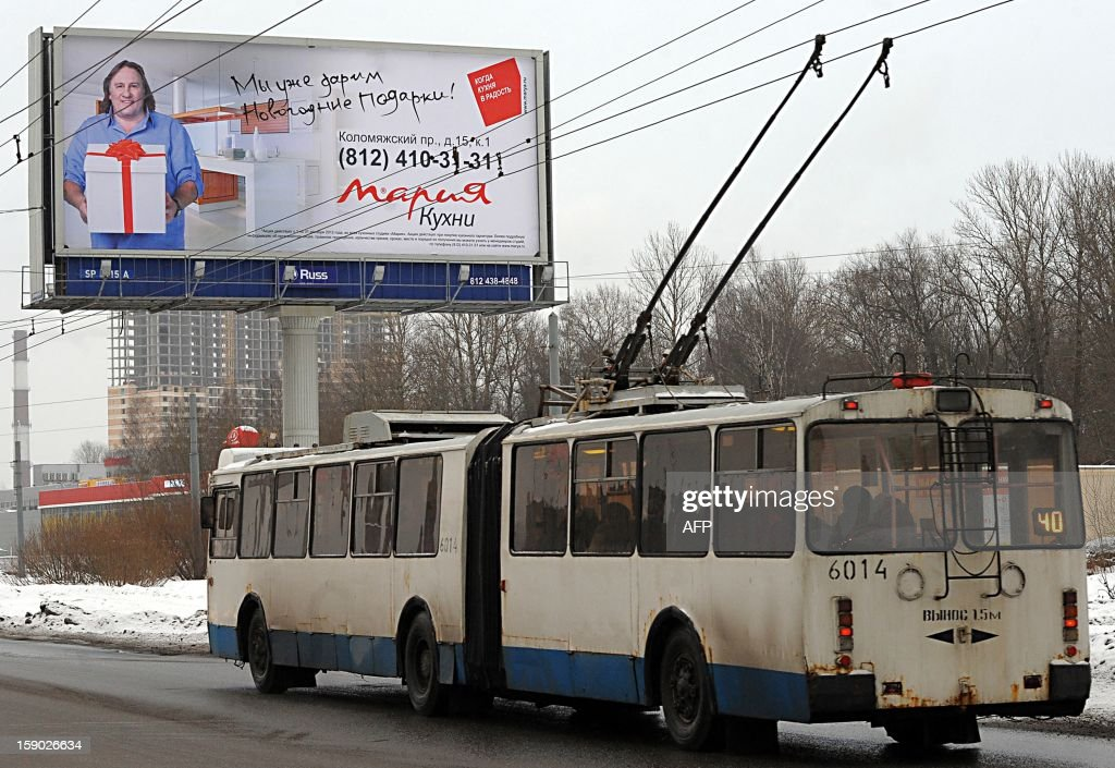 A bus drives by a commercial billboard showing French actor Gerard Depardieu in St. Petersburg on 6 January 2013. Gerard Depardieu, the French actor who threatened to quit his homeland to avoid higher taxes for the rich, has received a Russian passport and met with President Vladimir Putin, the Kremlin said on January 6. Depardieu met Putin, who earlier granted him citizenship, over a meal at the Russian leader's sumptuous residence in the palm-dotted Black Sea resort of Sochi, Putin's spokesman Dmitry Peskov told AFP. AFP PHOTO/ OLGA MALTSEVA
