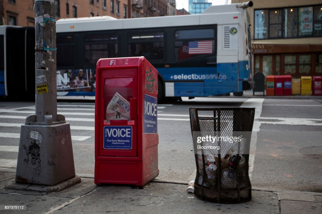 A bus drives past a distribution box for The Village Voice in the East Village neighborhood of New York, U.S., on Tuesday, Aug. 22, 2017. Peter Barbey, owner of The Village Voice since 2015, has decided to no longer produce a print edition of the alt-weekly publication. The company's announcement, made Tuesday afternoon, came as a surprise, a shock and a disappointment to the larger media industry on Twitter. Photographer: Michael Nagle/Bloomberg via Getty Images