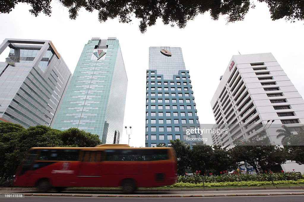 A bus drives past buildings in the financial district of Jakarta, Indonesia, on Tuesday, Jan. 8, 2013. Indonesia's rupiah weakened by the most in six months on concern the government's failure to meet its spending target last year will hamper economic growth and damp demand for local assets. Photographer: Dimas Ardian/Bloomberg via Getty Images