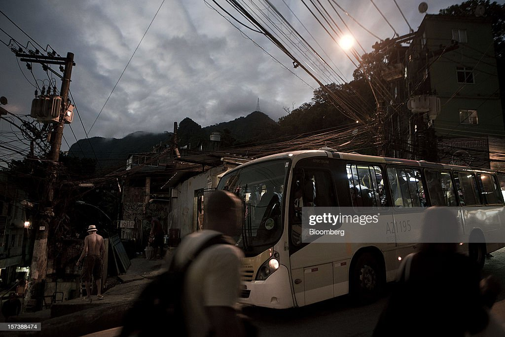 A bus drives past pedestrians on the street in the Rocinha slum of Rio de Janeiro, Brazil, on Wednesday, Nov. 28, 2012. About 56 percent of the 12 million people who live in slums like Rocinha were considered middle class in 2011, up from 29 percent in 2001, according to a study this year by Instituto Data Popular, a Sao Paulo-based research group. Photographer: Dado Galdieri/Bloomberg via Getty Images