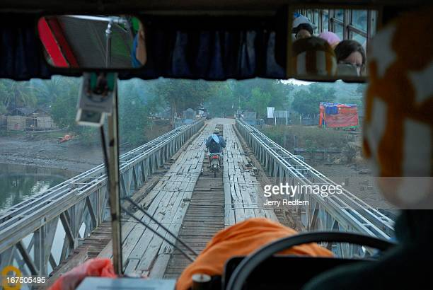 A bus drives slowly over the makeshift wooden roadbed on an old steel bridge in Ayerwaddy Division