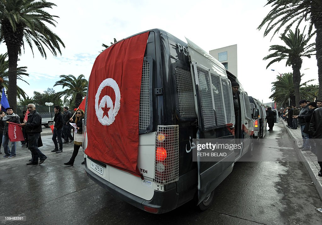 A bus is covered with a national flag as part of the festivities marking the second anniversary of the uprising that ousted long-time dictator Zine El Abidine Ben Ali on January 14, 2013 in Tunis. Tunisians marked two years since the revolution amid a climate of uncertainty marked by social tension, a weak economy, threats from jihadists and a political impasse.