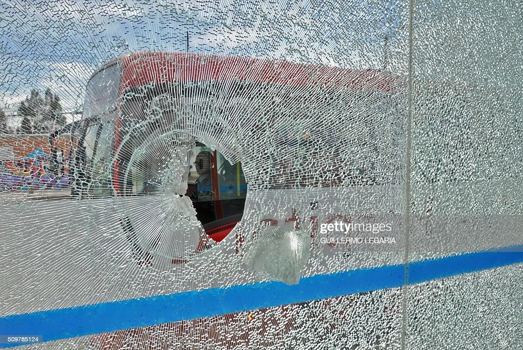 A bus is seen through a broken glass during a protest at the 'Transmilenio' station in southern Bogota, Colombia, on February 12, 2016. Users of public transportation blocked roads to protest what they consider poor service and high cost. Amid the protest several buses were damaged as well as stations destroyed and several demonstrators were detained by police after clashes. AFP PHOTO / GUILLERMO LEGARIA / AFP / GUILLERMO LEGARIA