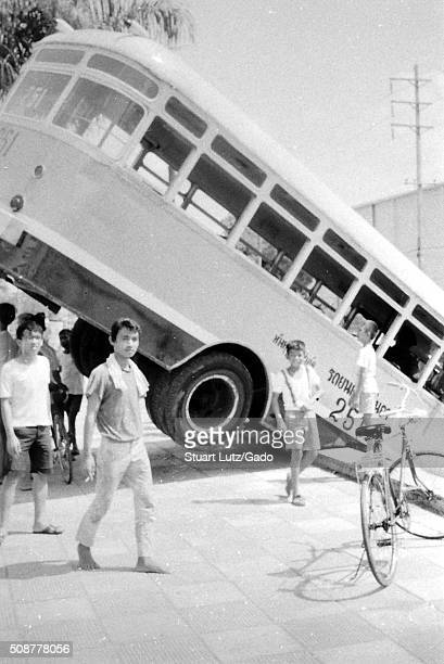 Bus leaning over the edge of a bridge in a city setting back tires in the air with a crowd of men and boys gathering around the bus Vietnam 1969