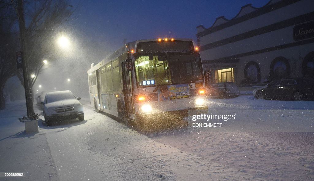 A NYC bus makes it's way down a snow covered street on January 23 2016 in New York A deadly blizzard with bonechilling winds and potentially...