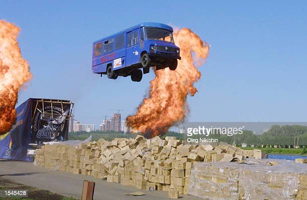 A bus operated by stuntmen jumps over a flame of fire at the Moscow International Festival of Stunts May 25 2002 in Moscow Russia The event is a...