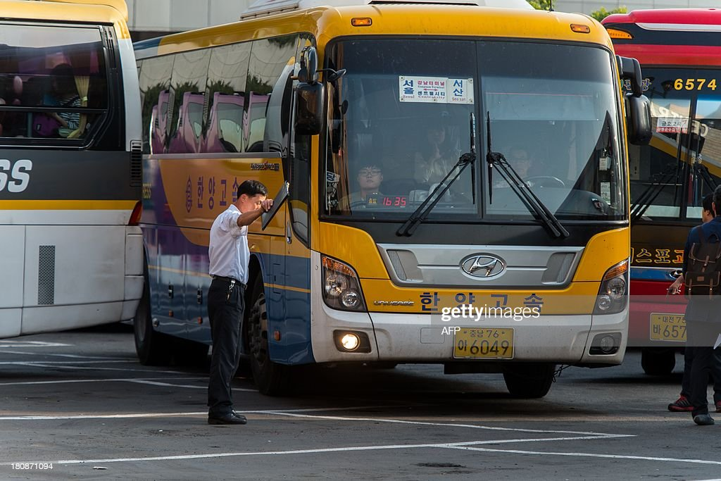 A bus operator (C) works at a bus terminal in Seoul on September 17, 2013 ahead of Chuseok, South Korea's biggest holiday, which lasts from September 18-20. Approximately thirty five million people are expected to travel to their home towns and villages across the country to visit relatives this year, an increase of 4.9 percent compared with last year's holiday.
