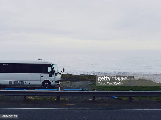 Bus Parked In Front Of Coastal Bay On Roadside