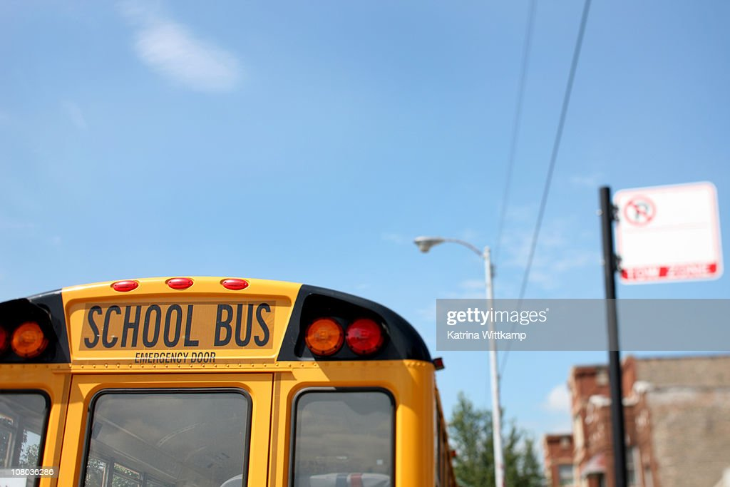 Bus parked outside of school : Stock Photo