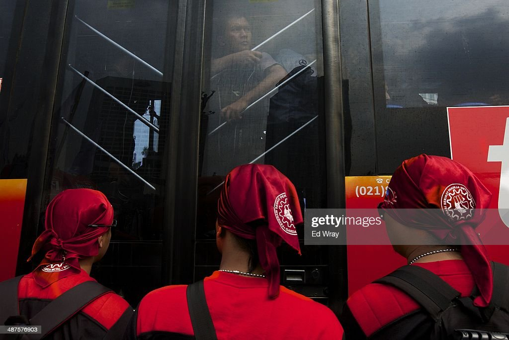 A bus passenger watches as he passes by members of an Indonesian Labour union protesting on a street in the central business district on May 1, 2014 in Jakarta, Indonesia. Protesters across Indonesia have organised rallies to demand higher wages, as Indonesia recognises its first national labour day holiday.