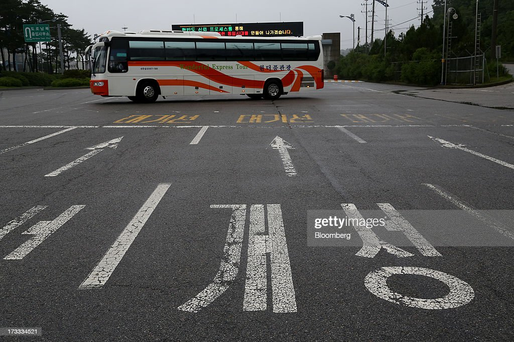 A bus passes behind road surface markings for North Korean city Gaeseong in front of a gate at the Customs, Immigration and Quarantine (CIQ) office, near the demilitarized zone (DMZ), in Paju, South Korea, on Friday, July 12, 2013. North Korea notified South Korea today that it has deferred two separate sets of talks on the tours and the family reunions it proposed yesterday, and said it wants to focus on the ongoing dialog to reopen the joint Gaeseong industrial zone, the Souths Unification Ministry said in an e-mailed statement. The two sides yesterday decided to hold talks in Gaeseong on July 15, which will be their third round in one week, on normalizing operations in Gaeseong after the North unilaterally recalled its workers in April. Photographer: SeongJoon Cho/Bloomberg via Getty Images