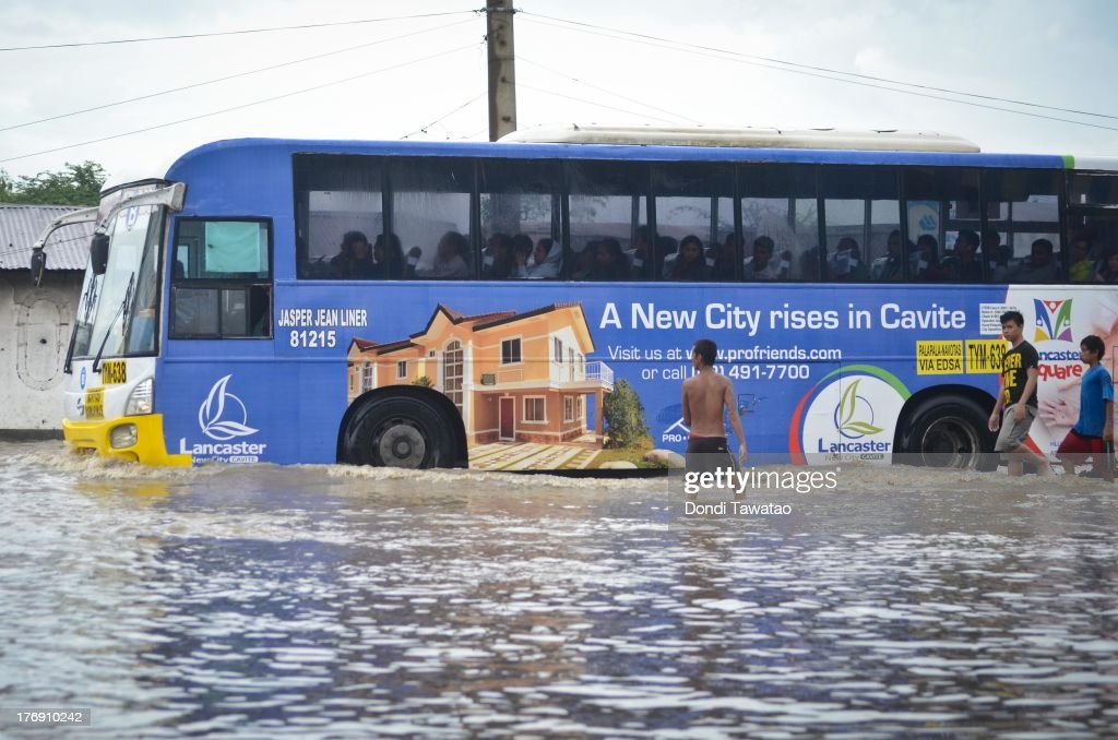 A bus passes through floodwaters during a downpour that inundated parts of Las Pinas on August 19, 2013 in Las Pinas City south of Manila, Philippines. Tropical storm Trami which was enhanced by monsoon rains swept overnight through the southern metropolitan cities of Manila and leaving huge parts of four provinces flooded forcing residents to evacuate their homes and seek shelter in evacuation centers. At least three fatalities were recorded with thousands more still needing to be rescued.