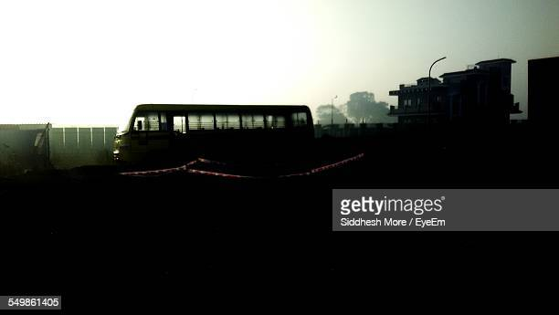 Bus Passing By Silhouette Field Against Clear Sky During Foggy Weather