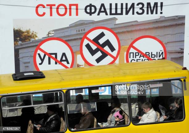 A bus rides past a referendum campaign billboard poster showing crossed signs of the UPA the Nazi swastika and the 'Right sector' and with text...