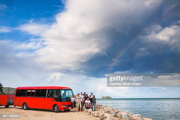 A bus stops at the base of a rainbow