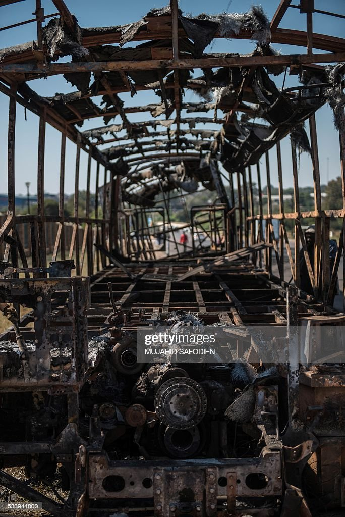 A bus torched during violent protest lies derelict as residents from the township of Hammanskraal rebuild their shacks after a forced eviction took place causing violent unrest on May 24, 2016 in Hammanskraal, North of Pretoria. Two people related to the eviction company were reportedly killed on May 23. / AFP / MUJAHID