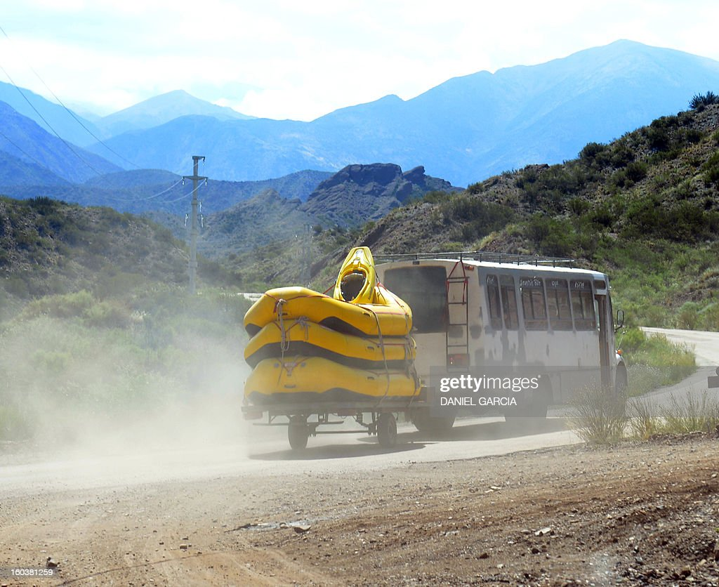 A bus transporting rafts for tourists to go paddling through the rapids in the muddy waters of the Mendoza river departs near Potrerillos, Argentina on January 29, 2013. AFP PHOTO / DANIEL GARCIA