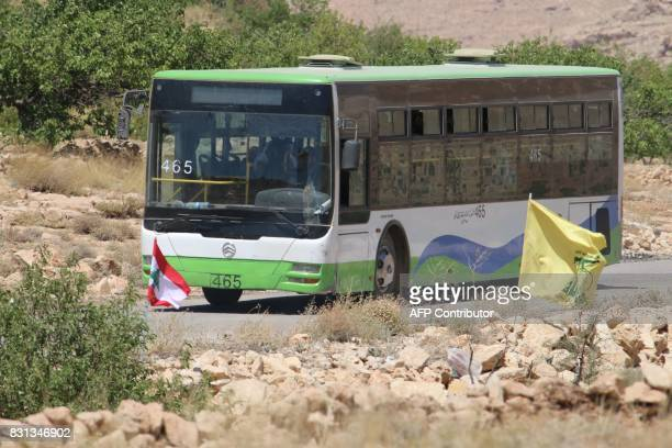 A bus transporting Syrian rebel fighters from northeastern Lebanon is seen driving past a Lebanese flag and a Hezbollah flag on August 14 2017 in a...