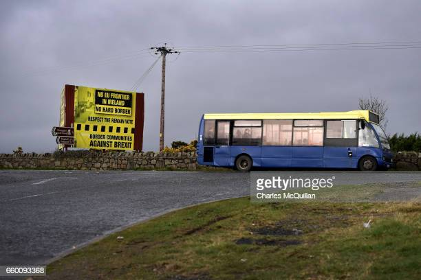 A bus travelling from southern Ireland in to Northern Ireland passes a Brexit protest sign along the stretch of road which seperates the two...