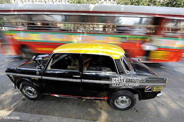 A bus whizzes past a Compressed Natural Gas taxi in Mumbai on January 27 2009 AFP PHOTO/ Sajjad HUSSAIN