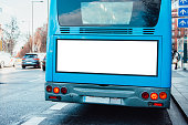 A bus with a blank billboard on its rear