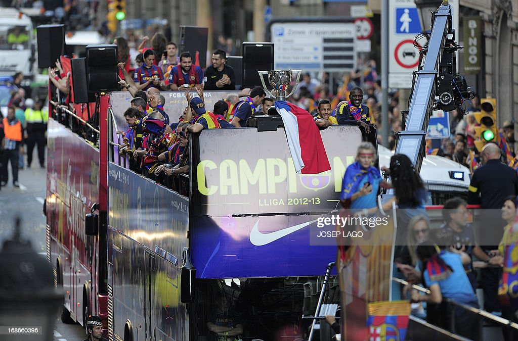 A bus with FC Barcelona's football players parade through a crowd of supporters as they celebrate in the streets of Barcelona on May 13, 2013, two days after their team won the Spanish league. The Catalans didn't even need to set foot on the pitch to seal the title on May 11 as Real Madrid's 1-1 draw with Espanyol meant Barca had already been crowned champions before their 2-1 win over Atletico Madrid on May 12, 2013.