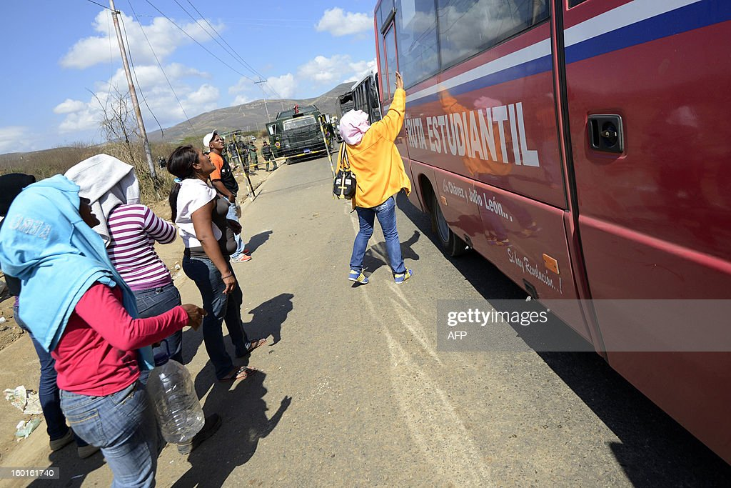 A bus with military forces leaves Uribana prison past relatives of inmates in Lara state, Venezuela, in January 27, 2013, two days after a riot. Security forces on Sunday regained full control over a prison in northwestern Venezuela and evacuated inmates after a riot left 61 dead and twice as many wounded, officials said. AFP PHOTO/Leo RAMIREZ