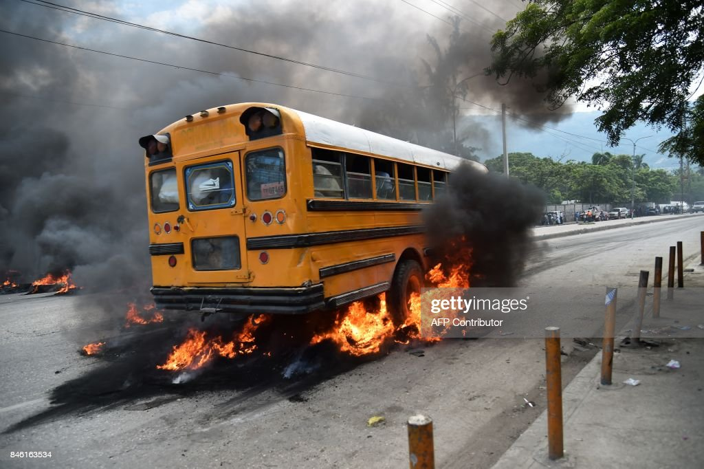A bus with passengers aboard drives over burning tires placed by demonstrators during an anti-government protest in the centre of the Haitian capital Port-au-Prince, on September 12, 2017. Demonstrators took to the streets to protest against the government and the new budget for 2017-2018, throwing stones at the police, setting tires on fire and blocking some streets. /