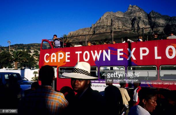 A bus with tourists drives along the beach road as the sun sets on January 1 2003 in Camps Bay outside Cape Town South Africa Camps Bay has some of...