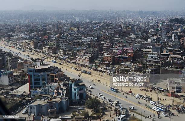 Buses and cars make their way down an avenue through a densely populated southeastern part of Nepal's capital Kathmandu on November 25 2014 Nepal's...