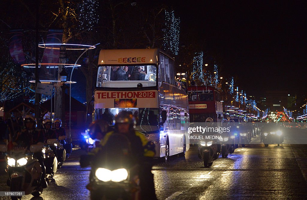 Buses are escorted in Paris streets during a ceremony to launch the 26th Telethon, France's biggest annual fund-raising event on December 7, 2012. The event, aiming at collecting funds for research on genetic diseases such as myopathy, a neuromuscular disease, will take place on December 7 and 8, 2011. AFP PHOTO MIGUEL MEDINA