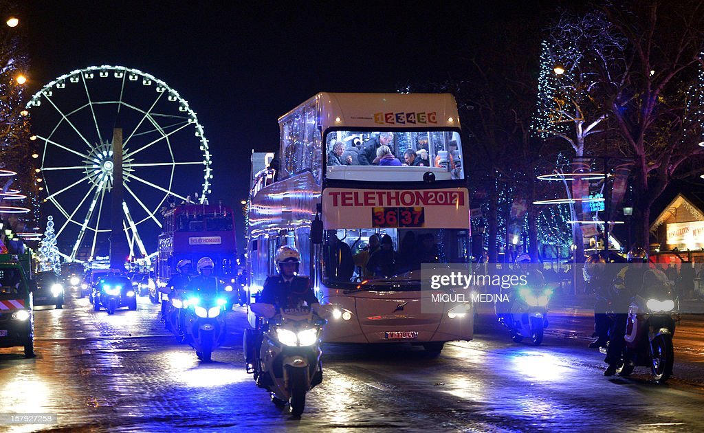Buses are escorted in Paris streets during a ceremony to launch the 26th Telethon, France's biggest annual fund-raising event on December 7, 2012. The event, aiming at collecting funds for research on genetic diseases such as myopathy, a neuromuscular disease, will take place on December 7 and 8, 2011.
