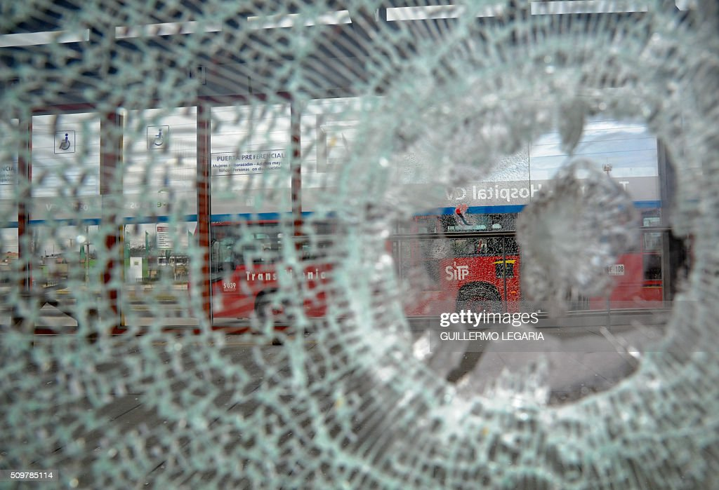 Buses are seen through a broken glass during a protest at the 'Transmilenio' station in southern Bogota, Colombia, on February 12, 2016. Users of public transportation blocked roads to protest what they consider poor service and high cost. Amid the protest several buses were damaged as well as stations destroyed and several demonstrators were detained by police after clashes. AFP PHOTO / GUILLERMO LEGARIA / AFP / GUILLERMO LEGARIA